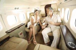 Smiling and happy couple seated in a private jet and toasting each other while heading on a trip